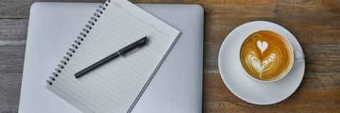Läppärin päällä vihko ja kynä, vieressä kuppi kahvia.